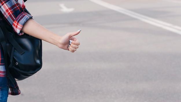 Close-up van de hand die van de vrouw duim op gebaar op straat tonen Gratis Foto