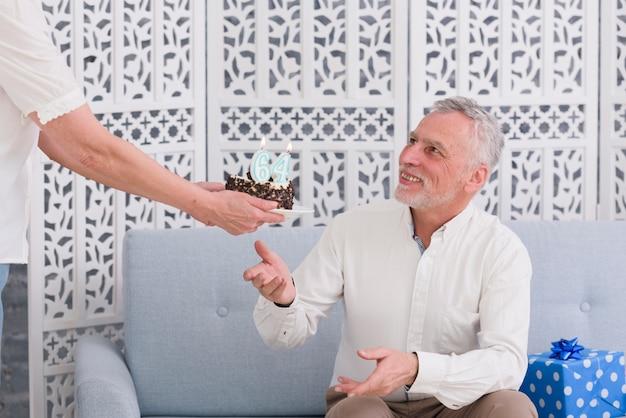Close-up van de hand die van de vrouw verjaardagscake geeft aan haar glimlachende echtgenoot Gratis Foto