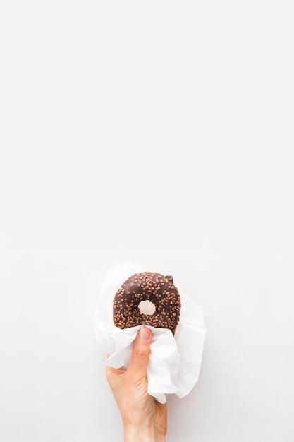 Close-up van de hand die van een persoon chocoladedoughnut in papieren zakdoekje over witte achtergrond houdt Gratis Foto