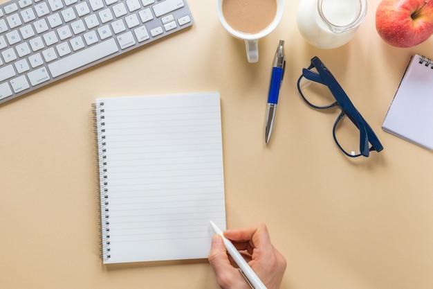Close-up van de hand die van een persoon op spiraalvormige blocnote met pen op beige bureau schrijft Gratis Foto