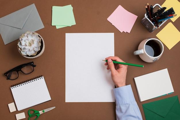 Close-up van de hand die van een persoon op wit leeg document met kantoorbehoeften op bureau schrijft Gratis Foto