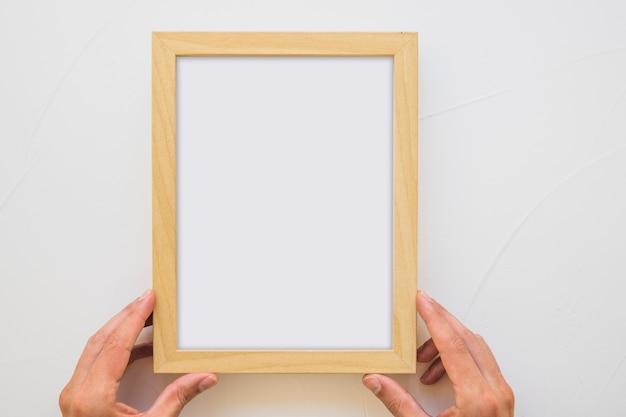 Close-up van de hand die van een persoon wit houten kader op muur houdt Gratis Foto