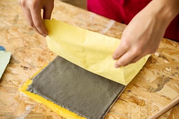 Close-up van de hand die van een vrouw gele stof over document pulp houdt Gratis Foto