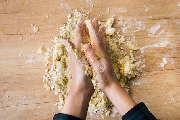 Close-up van de hand die van een vrouw het deeg voor het voorbereiden van italiaanse gnocchi op houten bureau kneden Gratis Foto