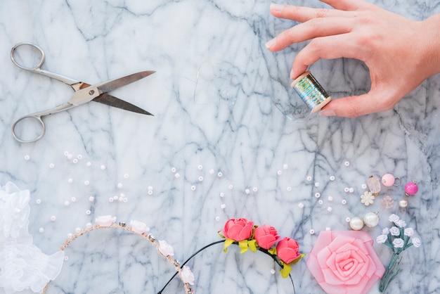 Close-up van de hand die van een vrouw zilveren spoelschaar houdt; kralen; lint roos en haarband op marmeren gestructureerde achtergrond Gratis Foto