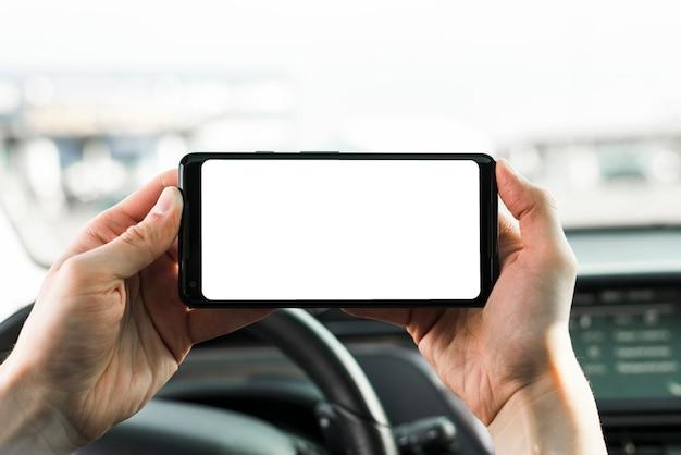 Close-up van de hand houden van mobiele telefoon met lege witte scherm in de auto Gratis Foto