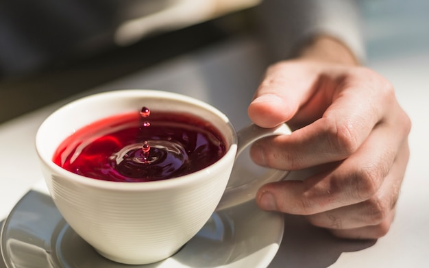 Close-up van de hand met een kopje vers gebrouwen rode thee beker Gratis Foto
