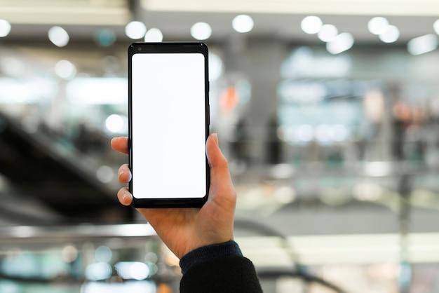 Close-up van de hand met witte lege weergave van slimme telefoon in winkelcentrum Gratis Foto