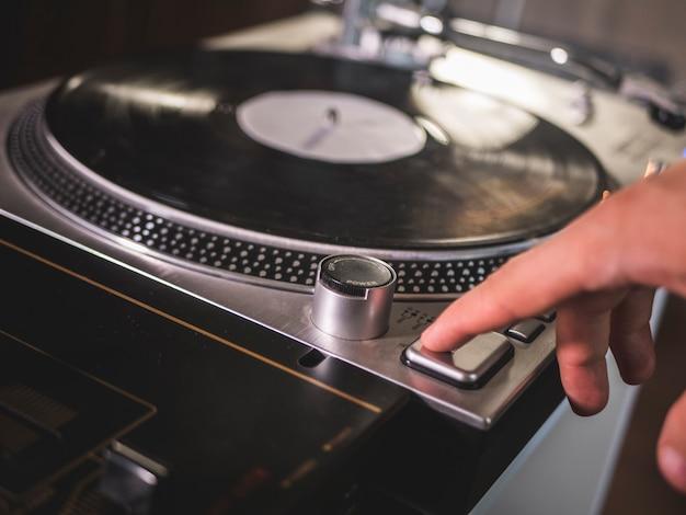 Close-up van de hand startspel knop op vintage vinyl records grammofoon speler draait Premium Foto
