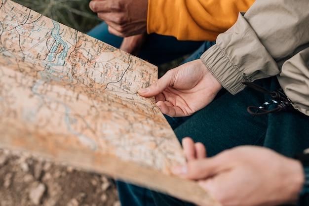 Close-up van de hand van de mannelijke wandelaar die de kaart houdt Gratis Foto