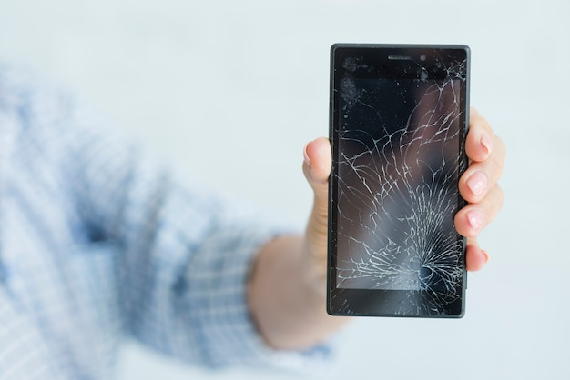 Close-up van de hand van de vrouw die het gebroken mobiele scherm toont Gratis Foto