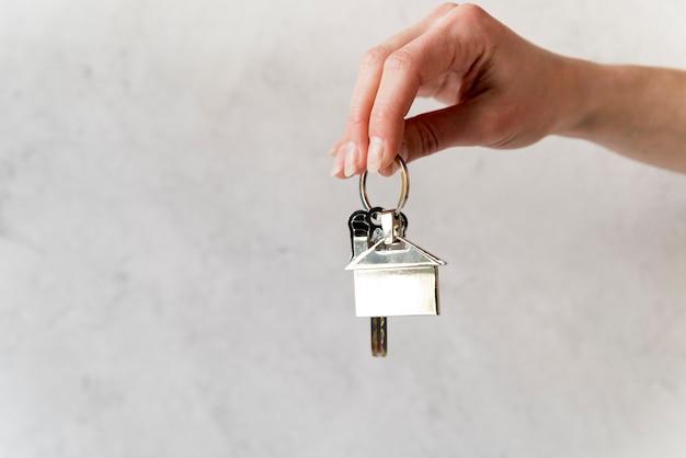 Close-up van de hand van de vrouw met zilveren huis sleutelhanger tegen betonnen muur Premium Foto