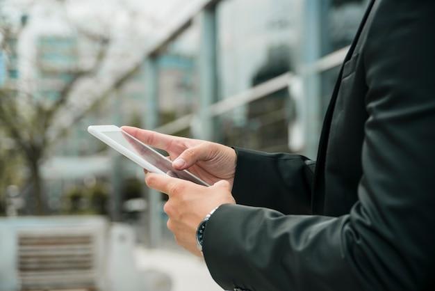 Close-up van de hand van de zakenman met behulp van de mobiele telefoon in de open lucht Gratis Foto
