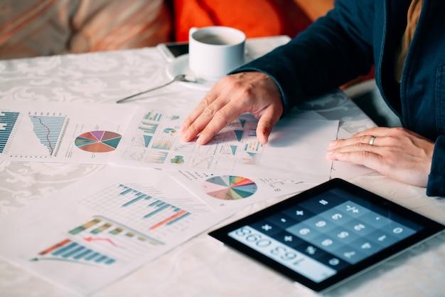 Close-up van de hand van een businessperson analyseren van factuur op digitale tablet via bureau, Premium Foto