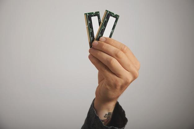 Close-up van de hand van een getatoeëerde man met twee ram-planken met chips op witte muur Gratis Foto
