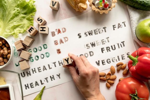 Close-up van de hand van een persoon die ongezonde tekst op papier met voedsel en blokken afdrukt Gratis Foto