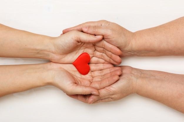 Close-up van de hand van een volwassen dochter en een oudere moeder die een hart samenhoudt Premium Foto