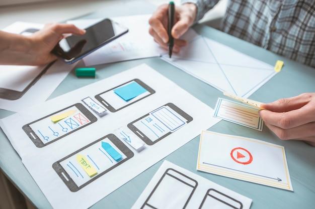 Close-up van de handen van een webdesigner ontwikkelen van toepassingen voor mobiele telefoons. Premium Foto
