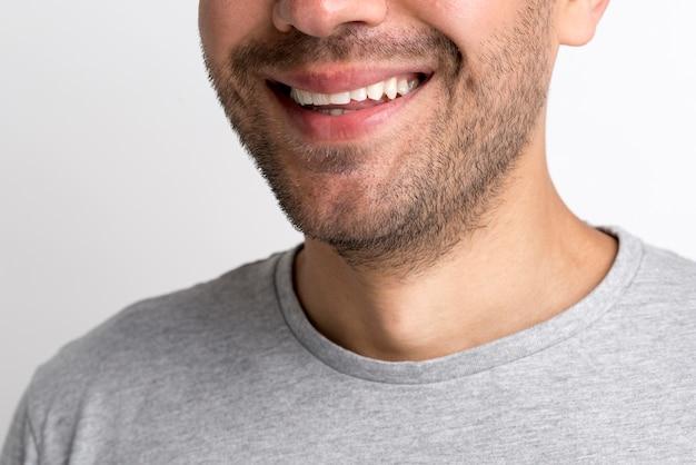 Close-up van de jonge glimlachende mens in grijze t-shirt tegen witte achtergrond Gratis Foto