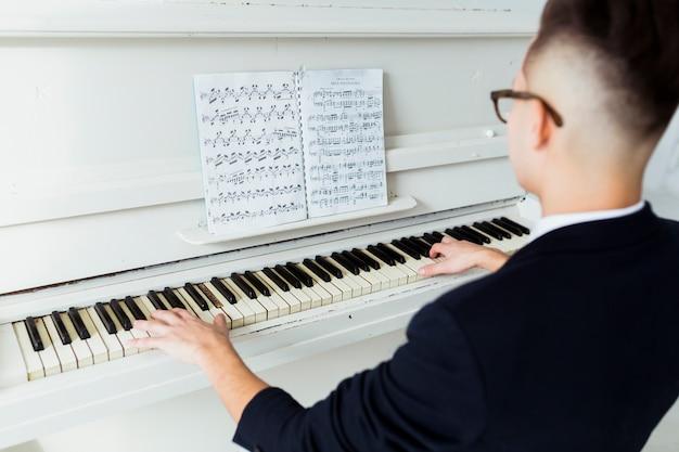 Close-up van de jonge man op zoek naar muzikale blad piano spelen Gratis Foto
