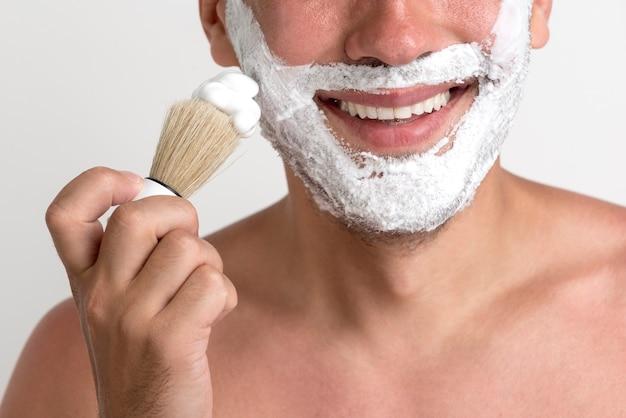 Close-up van de jonge man scheerschuim met borstel op gezicht toe te passen Gratis Foto