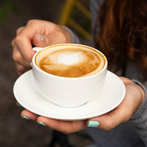 Close-up van de koffiekop van de vrouwenholding Gratis Foto