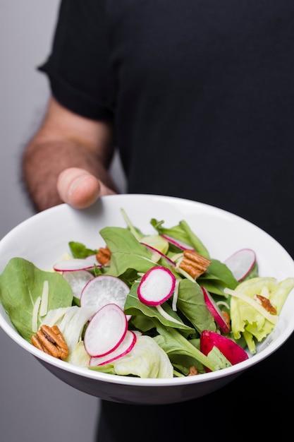 Close-up van de kom van de mensenholding salade Gratis Foto