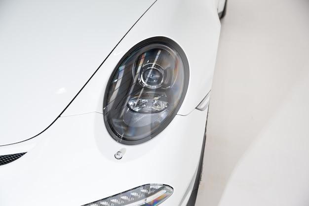 Close-up van de koplamp van een witte luxeauto onder de lichten tegen een grijze achtergrond Gratis Foto