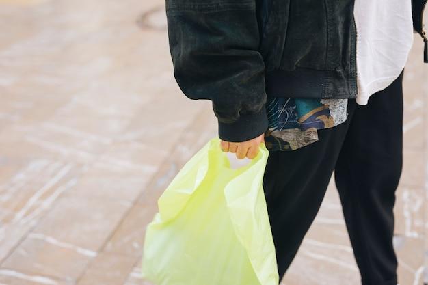 Close-up van de man die gele draagt â € <â € <plastic zak in de hand Gratis Foto
