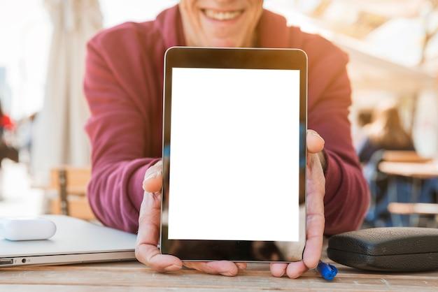 Close-up van de mens die digitale tablet met het lege witte scherm op houten lijst toont Gratis Foto