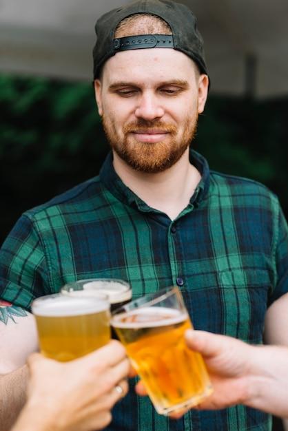 Close-up van de mens die glb draagt die bierglazen met vrienden roostert Gratis Foto