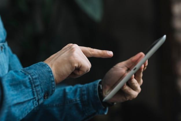 Close-up van de mens die vinger over de digitale tablet richt Gratis Foto