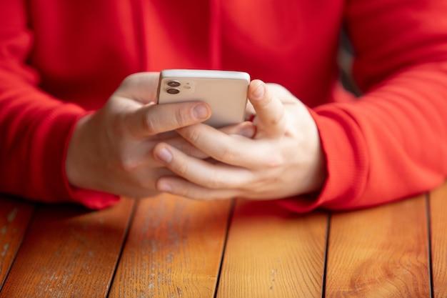 Close-up van de mens met behulp van mobiele slimme telefoon geïsoleerd op een witte muur. levensstijl, modern technologieënconcept. Gratis Foto