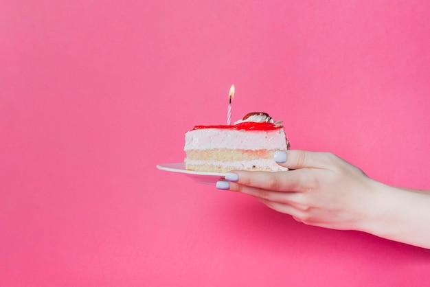 Close-up van de plak van de de holdingscake van de hand met aangestoken kaars op plaat over de roze achtergrond Gratis Foto