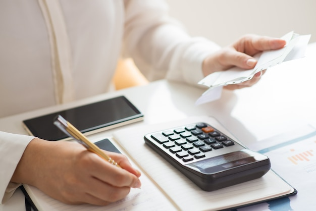 Close-up van de rekeningen van de persoonsholding en het berekenen van hen Gratis Foto