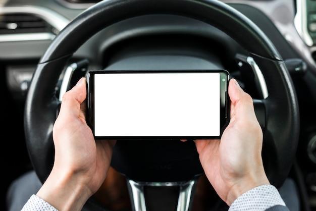 Close-up van de smartphone van de de handholding van een zakenman voor stuurwiel Gratis Foto