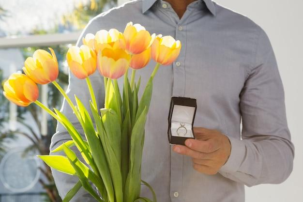 Close-up van de verlovingsring van de mensenholding en bloemboeket Premium Foto