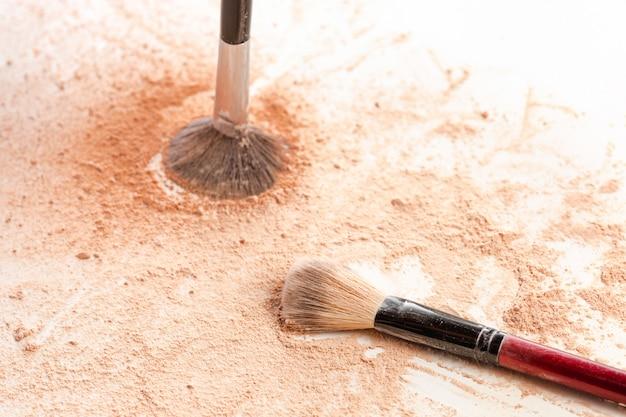 Close-up van de verpletterde minerale gouden kleur van het flikkeringspoeder met make-upborstel Gratis Foto