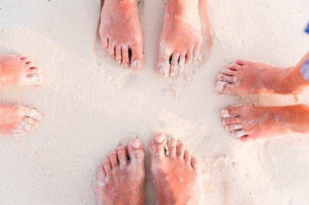 Close-up van de voeten van familie op het witte zandstrand Premium Foto
