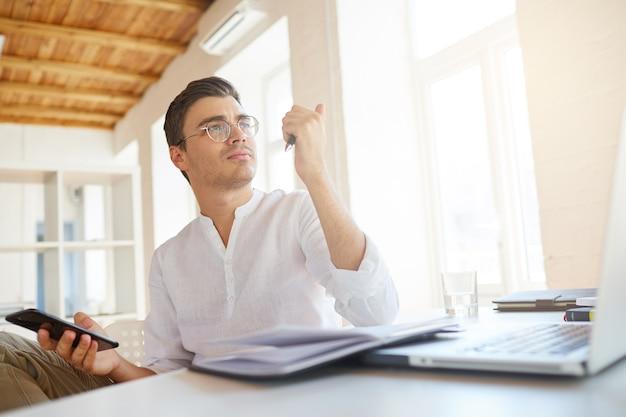 Close-up van doordachte ernstige jonge zakenman draagt een wit overhemd op kantoor Gratis Foto