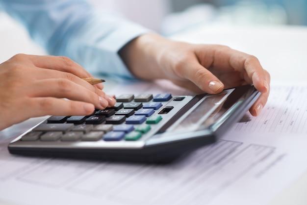 Close-up van econoom die en gegevens over calculator werken tellen Gratis Foto