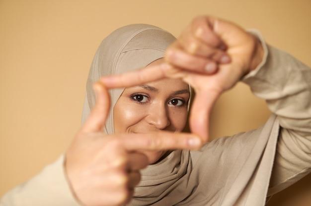 Close-up van een aantrekkelijke look van mooie arabische moslimvrouw in hijab door middel van vingerframes Premium Foto