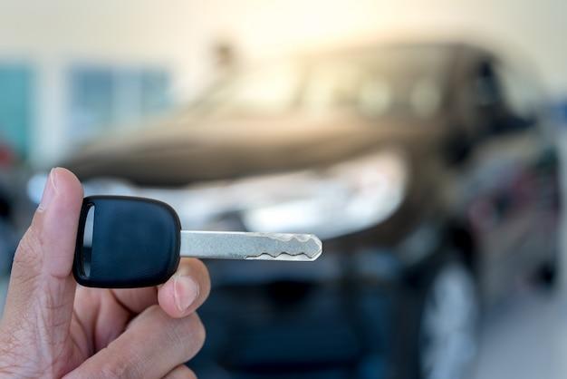 Close-up van een autosleutel - een jonge man die een nieuwe autosleutel in de autotoonzaal houdt, nieuwe sleutel Premium Foto