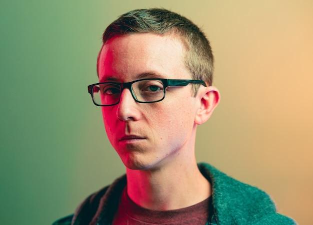Close-up van een blanke man met een pokerface die een bril met rood lichteffect draagt Gratis Foto