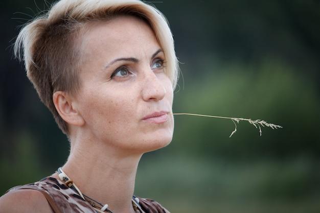 Close-up van een blonde vrouw op middelbare leeftijd met een aartje in haar mond. Premium Foto
