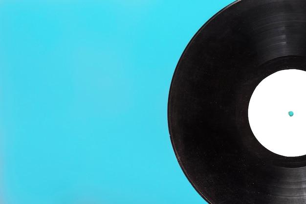 Close-up van één cirkelvormig vinylverslag op blauwe achtergrond Gratis Foto