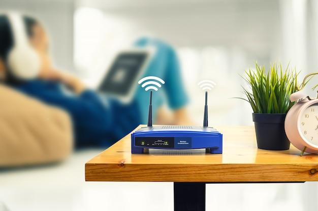 Close-up van een draadloze router en een mens die smartphone op woonkamer thuis bureau gebruiken Premium Foto