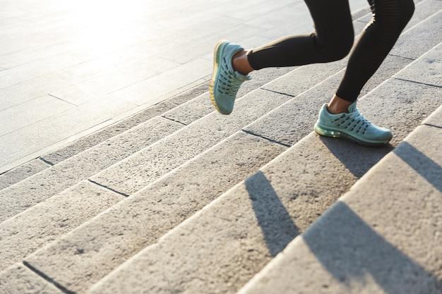 Close up van een fitness vrouw joggen de trap buitenshuis Premium Foto