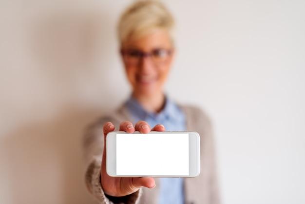 Close up van een gerichte weergave van een witte mobiele telefoon met wit scherm. wazig beeld van een meisje achter de telefoon die het vasthoudt. Premium Foto