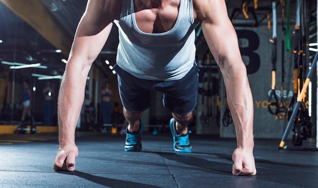 Close-up van een gespierde man hand doet push ups in de sportschool Gratis Foto